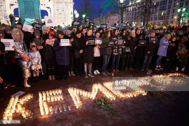 People light candles to commemorate the victims of Sunday's fire in a shopping mall in the Siberian city of Kemerovo in the center of Moscow on March...