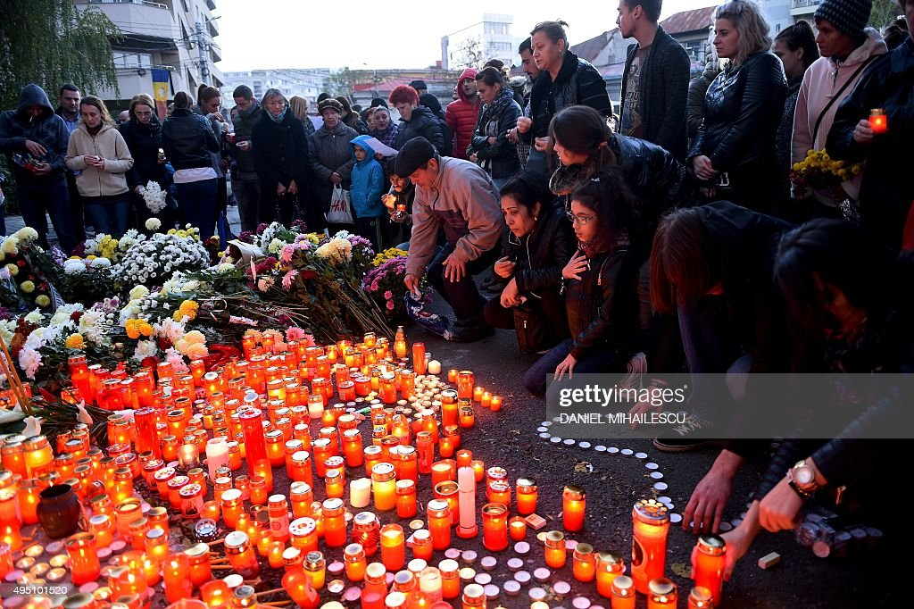 People light candles to commemorate the victims outside the nightclub Colectiv in Bucharest on October 31, 2015, a day after a mortal fire. At least 27 people were killed and more than 160 injured after a fire ripped through a nightclub in Bucharest late on Friday, in one of the worst accidents to hit the Romanian capital. MIHAILESCU