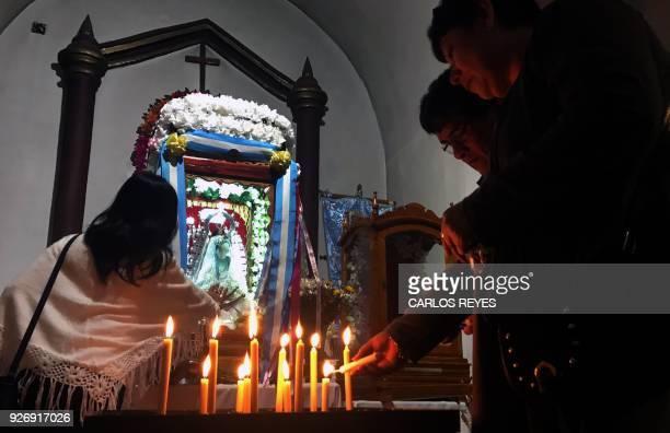 People light candles to the Virgin of Copacabana del Abra de Punta Corral at 'Nuesta Senora del Rosario' parish church in Tilcara Jujuy province...