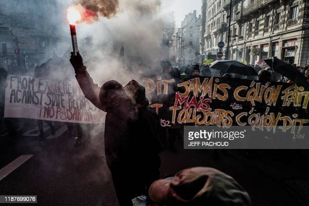 People light flares and hold banners during a demonstration on December 10, 2019 in Lyon as part of the sixth day of massive strike action over...