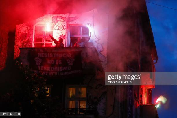 People light flares from the balcony of a house project in Berlin's Friedrichshain district, an annual hotspot for pre-Mayday activities on April 30,...