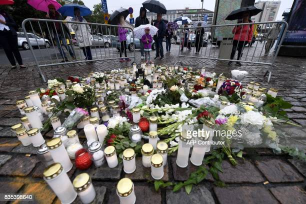 People light memorial candles at the Turku Market Square for the victims of a stabbing spree on August 19 2017 in Turku Police are now investigating...