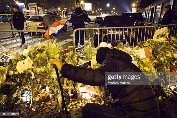 People light the candles to commemorate the victims of Charlie Hebdo and kosher supermarket in front of HyperCacher supermarket at Porte de Vincennes...
