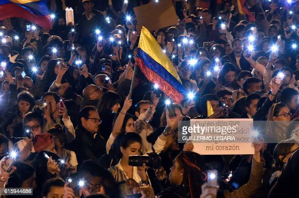 TOPSHOT People light their cellphones during a march for peace in Bogota on October 20 2016 Colombian President Juan Manuel Santos winner of this...