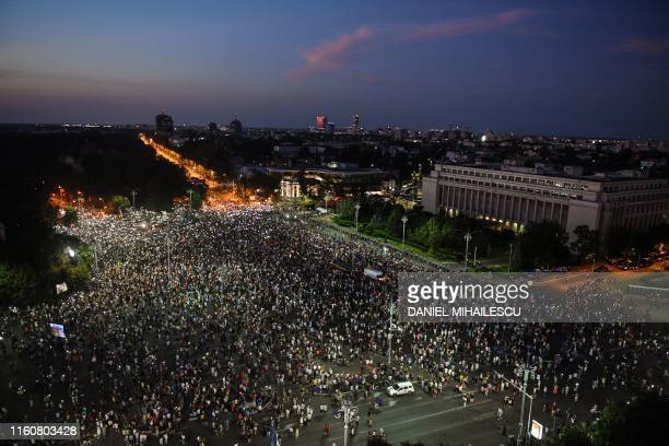 People light their mobile phones as they protest against the government and the Social Democratic ruling Party in front of the Romanian Government...