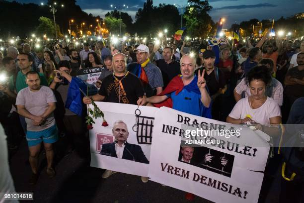 People light their phone lights and hold a poster depicting Liviu Dragnea leader of the ruling leftwing social democrat party and president of the...