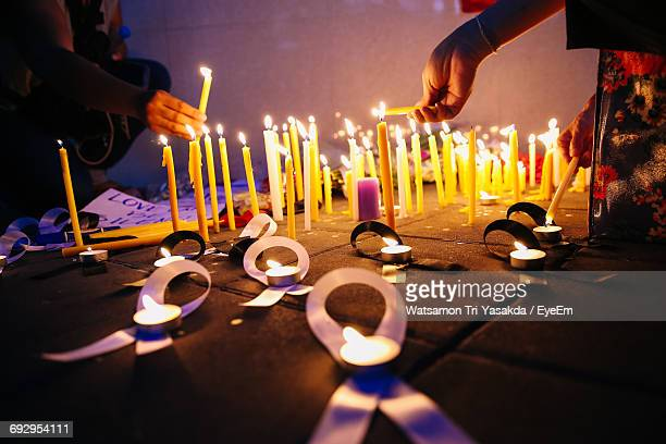 People Lighting Candles During Candlelight Vigil At Night