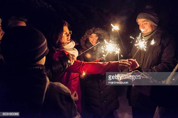 People lighting sparkling Bengal fire outdoors at night in winter.