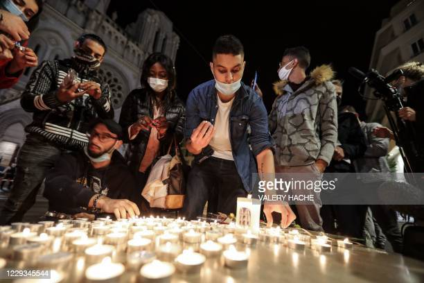 People lights candle outside the Notre-Dame de l'Assomption Basilica in Nice on October 29, 2020 in tribute to the three victims of a knife attacker,...