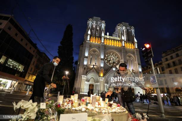 People lights candle outside the Notre-Dame de l'Assomption Basilica in Nice on October 30 a day after a knife attacker killed three people, cutting...