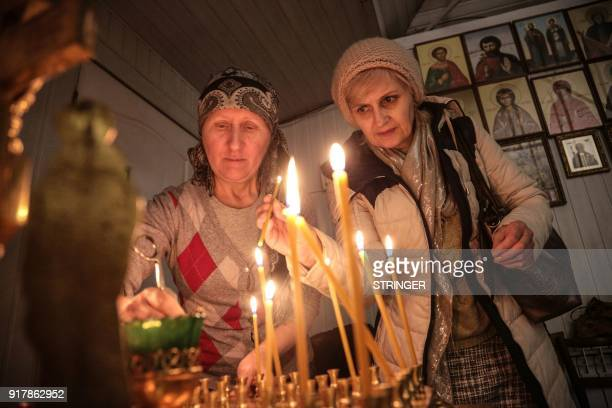 People lights candles during a church service in Simferopol on February 13 in commemoration of the victims of the plane crash The Antonov An148 plane...