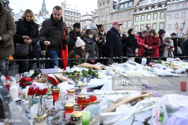 People lightup candles and deposit flowers during a gathering around a makeshift memorial at Place Kleber in Strasbourg on December 16 2018 to pay a...