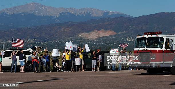 People line Old Ranch Road to cheer for the firefighters returning from a shift of fighting the Black Forest Fire Sunday June 16 outside the fire...