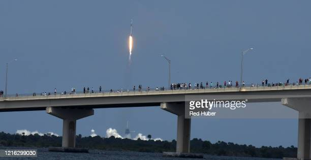 People line the AMax Brewer Causeway to watch the launch of a SpaceX Falcon 9 rocket from Cape Canaveral Florida May 30 2020 in Titusville Florida...