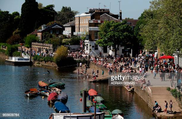 People line the banks of the River Thames as they soak up the sun in Richmond south west London on May 7 2018 Temperatures on Monday were predicted...