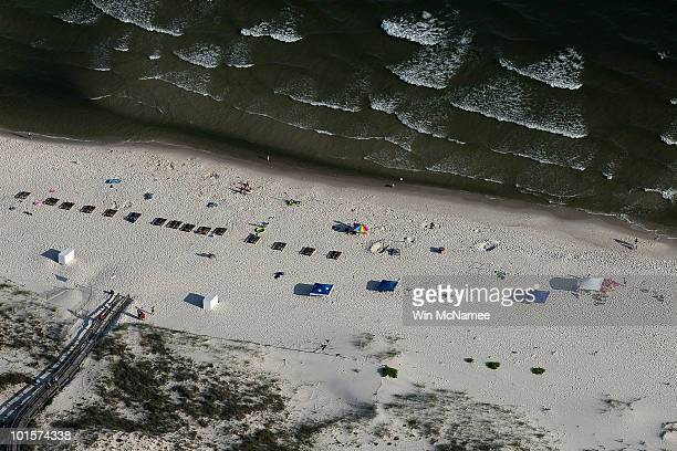 People line the beach June 2 2010 in Gulf Shores Alabama Oil believed to be related to the Deepwater Horizon accident began to appear yesterday on...