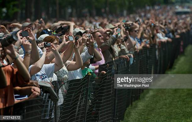 People line the fenced off grass areas to watch as World War II planes fly over the National Mall to makr the 70th anniversary of Victory in Europe...
