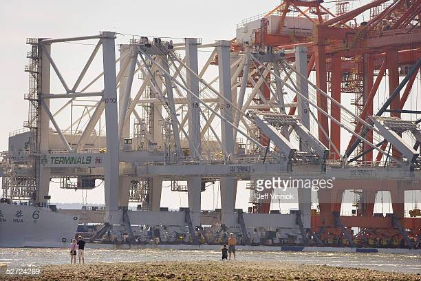 People line the shores of the Burrard Inlet as three of the world's largest Super PostPanamax Cranes float past into harbour April 27 2005 in...
