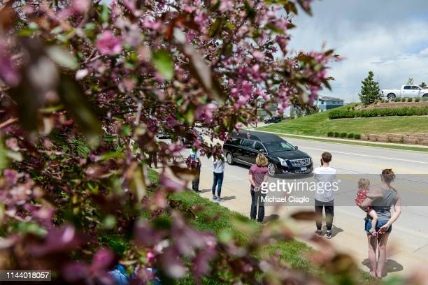 People line the street as a hearse carrying the body of Kendrick Castillo heads toward a celebration of life ceremony at the Cherry Hills Community...
