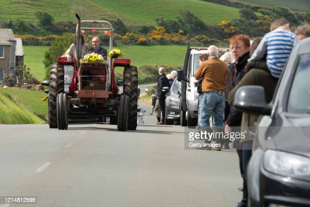 People line the street for Michael Quirk's funeral which is being lead by a man driving a tractor on May 20 2020 in Douglas Isle of Man The Isle of...