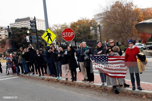 People line the streets to pay their respects as the hearse with the casket of former President George HW Bush passes by on the way to Andrews Air...