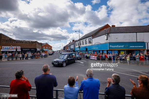 People line the streets to pay tribute to Jack Charlton as his funeral cortege passes through his childhood home town on July 21 2020 in Ashington...