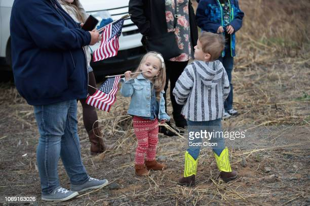 People line the tracks along a rural road as they wait for the train carrying the casket of former President George HW Bush to his final resting...