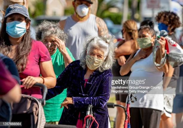 People line up along the 1200-block of Rivera Street at the Boys & Girls Club of Anaheim to receive free food in Anaheim on Tuesday, July 14, 2020....