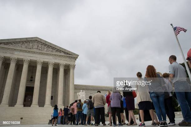 People line up as they wait to enter the US Supreme Court October 11 2017 in Washington DC On Tuesday the US Supreme Court dismissed one of two cases...