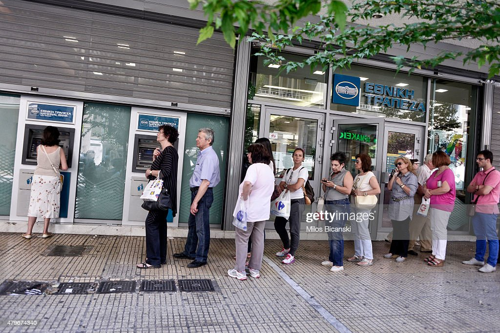 People line up at an ATM machine outside a bank on July 6, 2015 in Athens Greece. Politicians in Europe and Greece are planning emergency talks after Greek voters rejected EU proposals to pay back it's creditors creating an uncertain future for Greece. Finance minister Yanis Varoufakis resigned hours after the vote saying that it was felt his departure would be helpful in finding a solution..