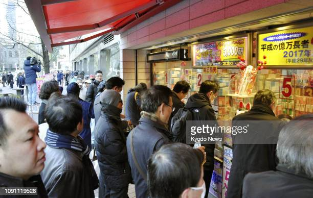 People line up at lottery booths in Tokyo's Ginza shopping district on Jan. 30 as sales of the Valentine's Day Jumbo lottery tickets started the same...