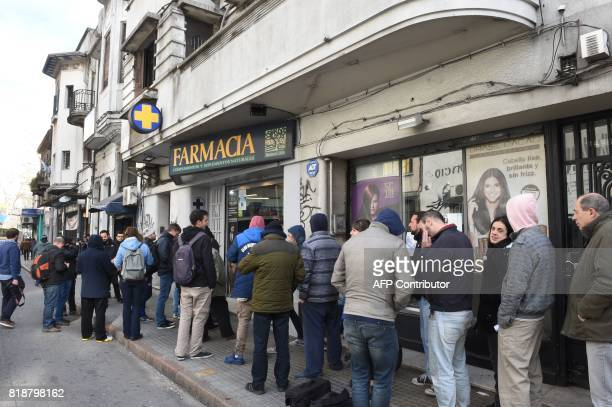 people line up early morning in front of a pharmacy to buy marijuana in Montevideo on July 19 2017 Pharmacies in Uruguay start selling marijuana from...