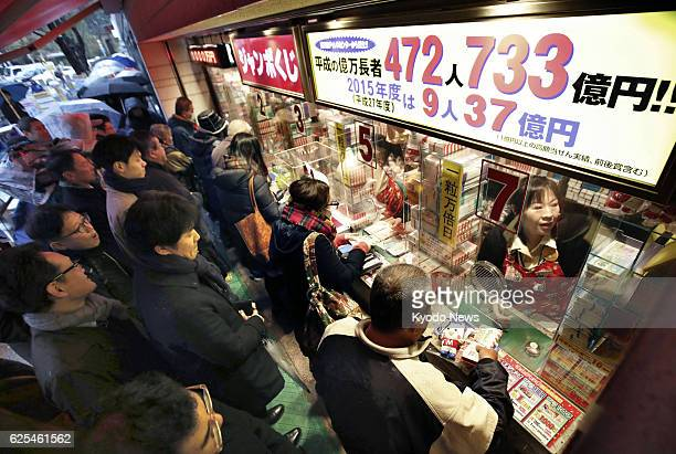 People line up in front of a booth in Tokyo's Ginza commercial district to buy the yearend 'Jumbo' lottery tickets which went on sale on Nov 24 2016...