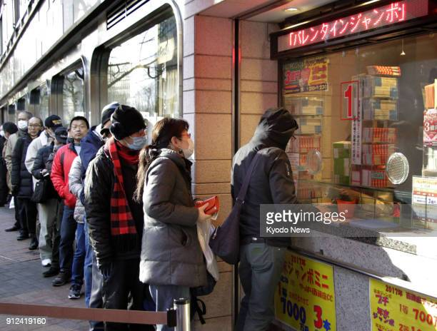 People line up in front of a lottery booth in Tokyo's Ginza commercial district on Jan 31 as sales of 'Valentine Jumbo' lottery tickets started the...