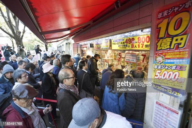 People line up in front of a lottery booth in Tokyo's Ginza district on Nov. 20 as sales of year-end lottery tickets started the same day. Purchasers...