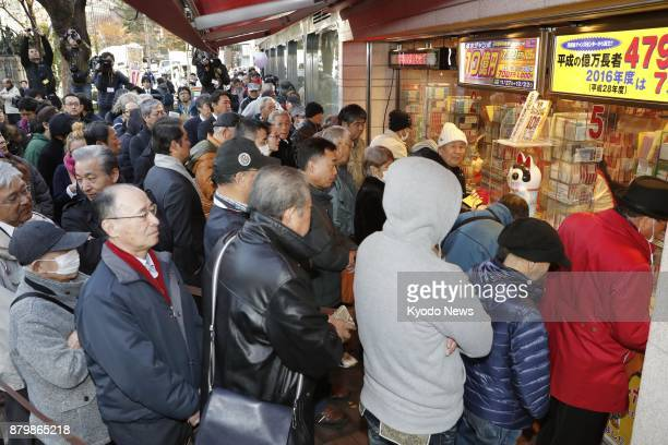 People line up in front of a lottery booth in Tokyo's Ginza district on Nov 27 as sales of yearend 'Jumbo' lottery tickets started the same day The...