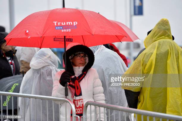 People line up in the rain and icy weather outside the SNHU arena hours ahead of President Donald Trump's rally in Manchester New Hampshire on...