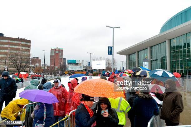 People line up in the rain and icy weather outside the SNHU arena hours ahead of President Donald Trump's rally in Manchester, New Hampshire on...