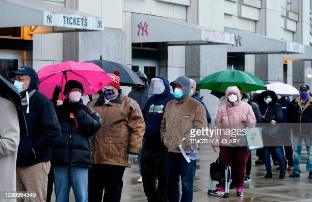 People line up in the rain outside the Yankee Stadium on February 5, 2021 in New York as the Stadium is turned into a mass Covid-19 vaccination site,...