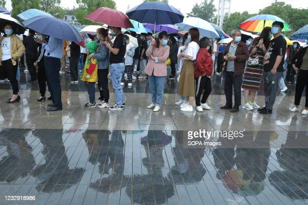 People line up in the rain to get vaccinated at the sports center of Fuyang Normal University. Recently, a number of positive cases of covid-19 have...