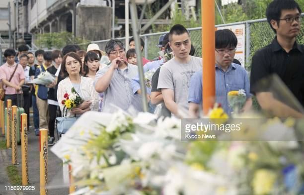 People line up near an alter set up near the site of a Kyoto Animation Co studio in Kyoto on July 21 three days after a man set the threestory...