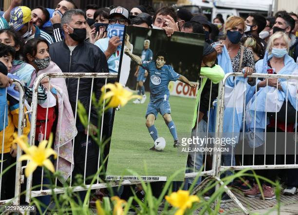 People line up on November 26, 2020 outside the presidential palace in Buenos Aires to pay tribute to football legend Diego Maradona's coffin which...