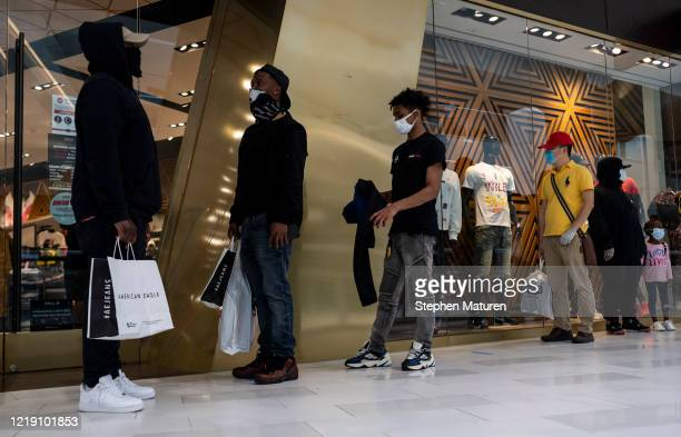People line up outside a store which is at capacity in the Mall of America on June 10, 2020 in Minneapolis, Minnesota. Today marks the first day the...