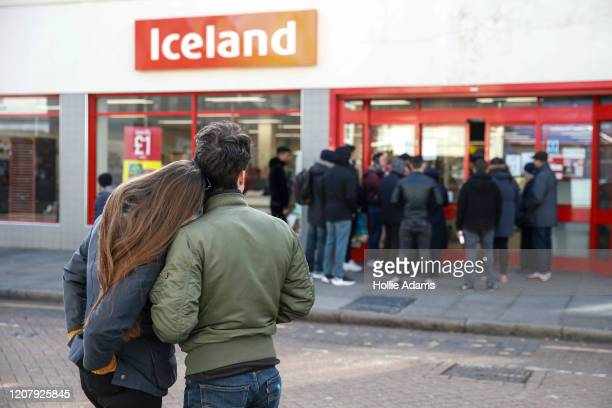 People line up outside an Iceland supermarket on Roman Road in Bow on March 21 2020 in London England Londoners are feeling the impact of shutdowns...