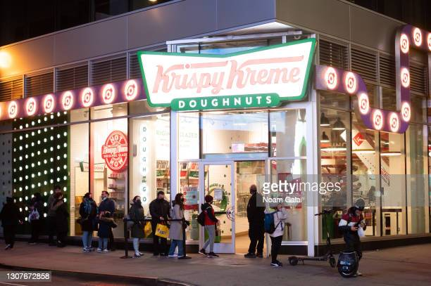 People line up outside Krispy Kreme in Times Square amid the coronavirus pandemic on March 17, 2021 in New York City. After undergoing various...