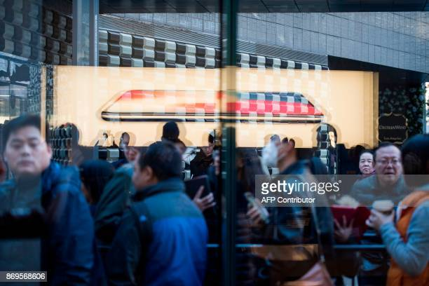 People line up outside the Apple store to get their hands on the new iPhone X in Beijing on November 3 2017 / AFP PHOTO / FRED DUFOUR