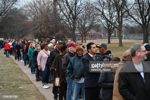 People line up to attend a campaign rally for Democratic presidential candidate Joe Biden at Renaissance High School in Detroit, Michigan on March 9,...