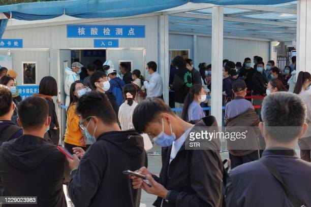 People line up to be tested for the COVID-19 coronavirus in Yantai, in China's eastern Shandong province on October 12 following a new outbreak of...