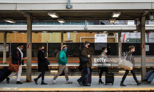 People line up to board a train at South Station in Boston on Nov. 25, 2020. The station was bustling with travelers on the Eve of Thanksgiving,...