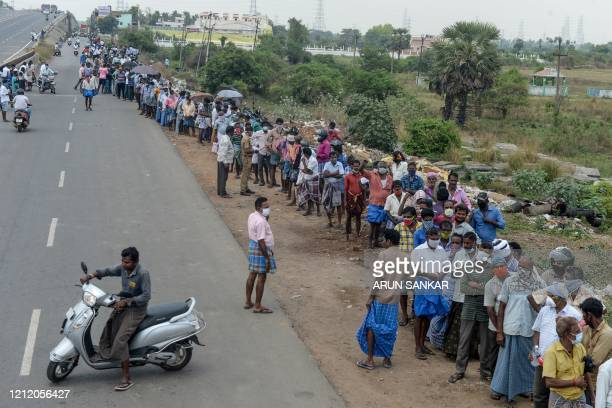 People line up to buy alcohol at a liquor shop after the government eased a nationwide lockdown imposed as a preventive measure against the COVID19...